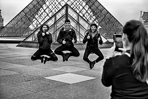un groupe de jeunes gens se photographient avec leur téélphone portable devant la pyramide du louvre à paris, nomophobie