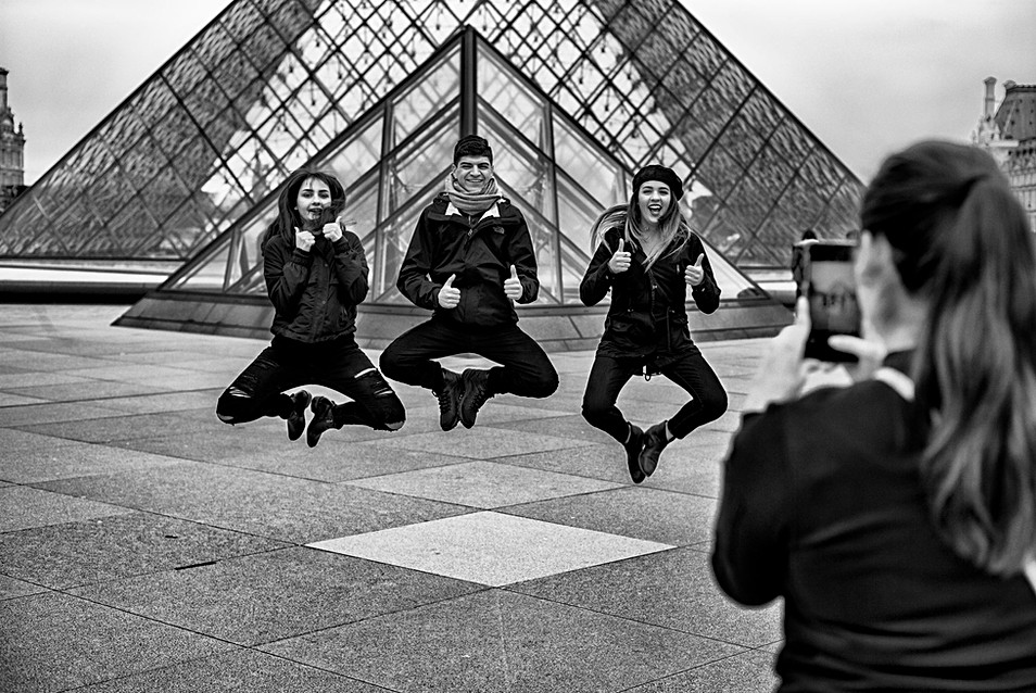 a group of young people photograph themselves with their mobile phones in front of the pyramid of the louvre in paris, nomophobia