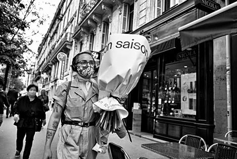 jeune femme dans une rue de paris porte un masque de protection sur le visage, elle a dans les bras un bouquet de fleurs, photo de rue laurent delhourme