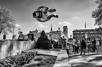 place de l'hotel de ville in paris, a man jumps in front of the crowd, notre dame in the background, black and white photo by delhourme