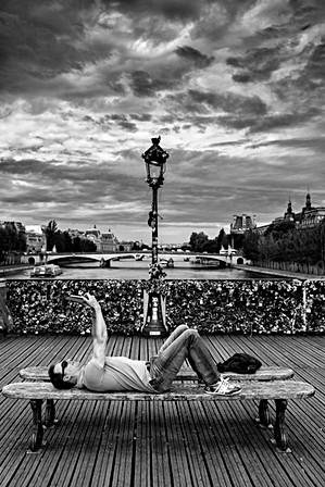 un homme se prend en photo avec son smartphone sur un pont de paris, nomophobie, photo humaniste en noir et blanc de laurent delhourme
