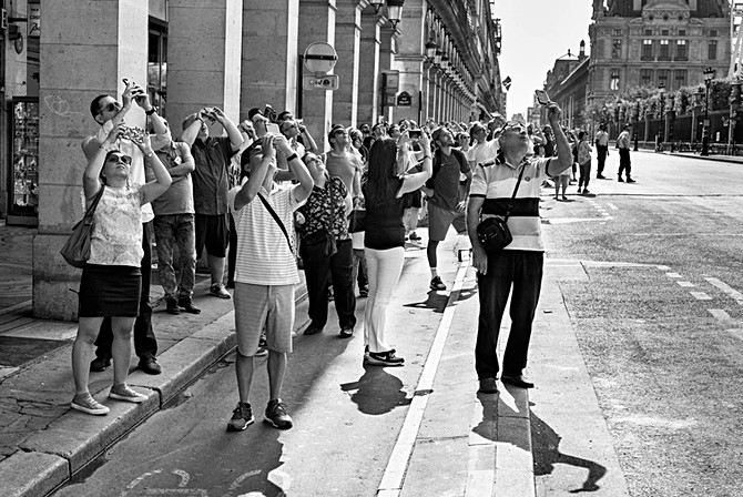 un groupe de personnes regardent passer le défilé du 14 juillet rue de rivoli à paris, ils prennent des photos avec leurs smartphones