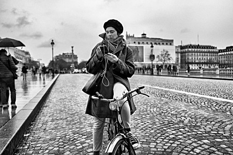 a young woman on her bicycle is stopped on the road to send a message with her iphone, center of paris, addiction