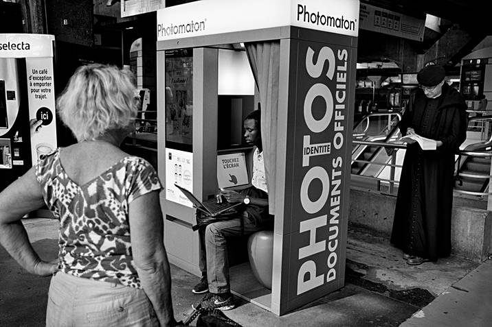 montparnasse station in paris in front of a photo booth, a woman waits her turn, a man with his computer sits with his computer, behind the booth a priest reads a book
