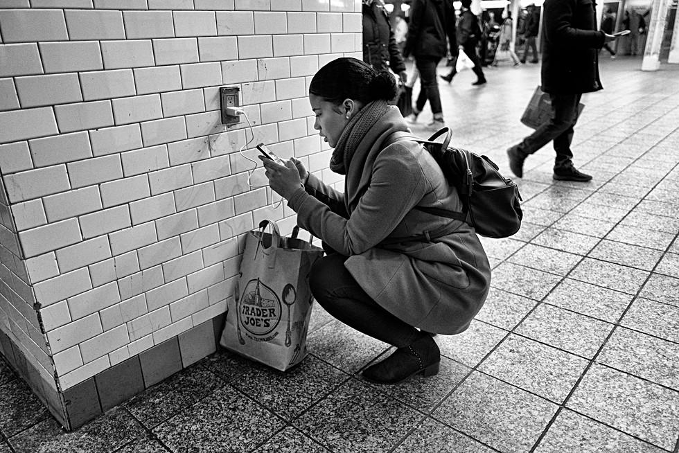 couloir du métro de new-york une femme a branché son téléphone sur une prise pour le recharger, auteur laurent delhourme