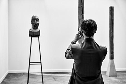 dans une exposition un homme fait des photos d'une statue avec son smartphone, photographie delhourme