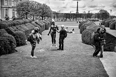 at the Tuileries Garden in Paris a couple kiss while another takes a photo around a statue, black and white street photography
