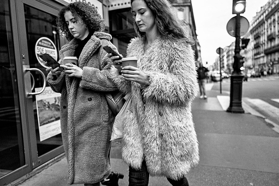 two young women walking in the street they both have smartphones, they look very similar, mimethism, phone addiction