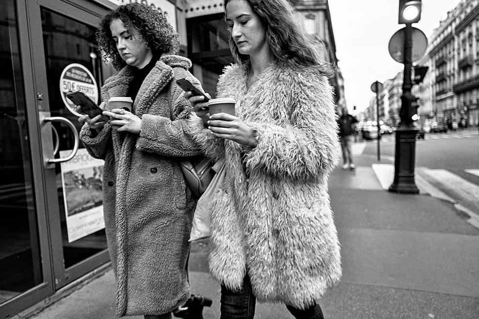 deux jeunes femmes marchent dans la rue elles ont toutes les deux un smartphones, elles se ressemblent beaucoup, miméthisme, addiction téléphone