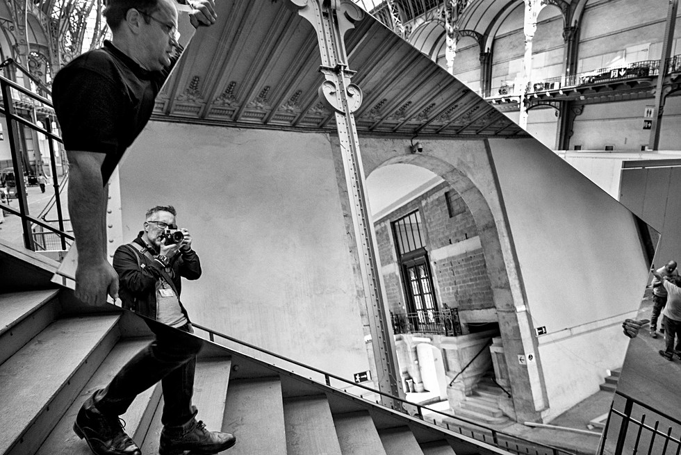 le photographe laurent delhourme fait un selfie dans un miroir au grand palais à paris, on ne voit que le haut de son corps, la photo est en noir et blanc