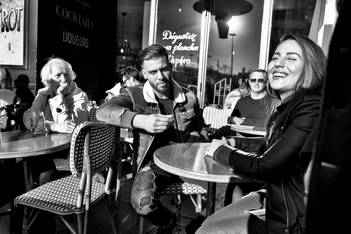 a couple at a bar terrace, the young woman is joyful, the people around them are looking at them, human photo by laurent delhourme