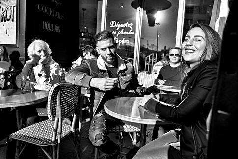 un couple à une terrasse de bar, la jeune femme est joyeuse, les gens autour d'eux les regardent, photo humainste de laurent delhourme