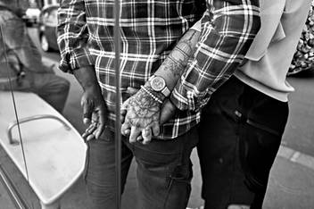 in a street of paris a couple hold hands seen from the back in close-up, the woman has a tattoo on the arm, black and white image by the humanist photographer delhourme