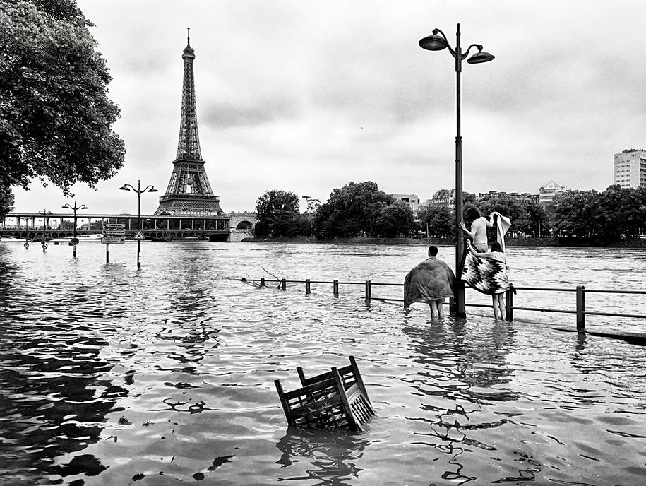 on the banks of the seine in flood in paris, the eiffel tower in the background in the foreground a group of young people are going to bathe while the river overflows, street photo by laurent delhourme