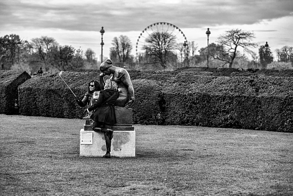 au jardin des tuileries un couple de femme font un autoportrait devant une statue avec un iphone, photo noir et blanc par laurent delhourme