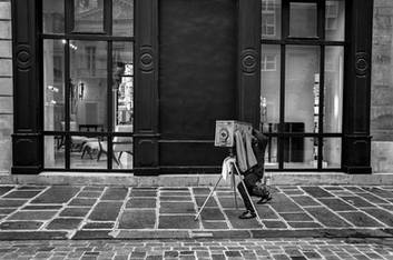 a photographer with his old wooden photo room makes an image in a street of paris