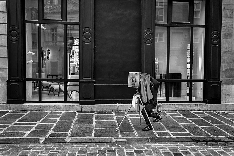 un homme fait des photos avec une vieille chambre photo en bois, il a un tissu noir sur la tête, il est dans paris, laurent delhourme auteur