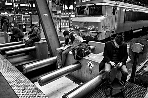 on the platform of the Gare du Nord in Paris, people wait for their trains while they are with their smartphone samsung
