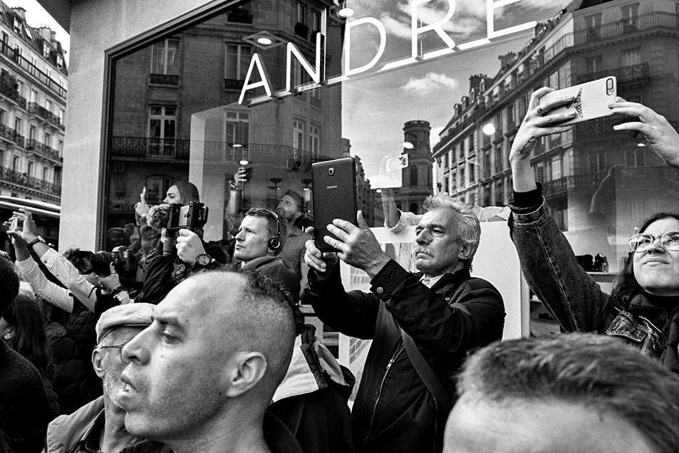 a group of people in front of a store window, they take pictures of what is happening in the street, rip jacques chirac