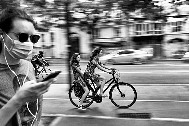 on a bicycle path in paris a woman carries her daughter on her bicycle, a person in the foreground is on the phone she wears a covid mask