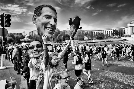 The marathon of paris a young girl holds pictures of her dad in her hands to encourage her. black and white photo in the street by laurent delhourme