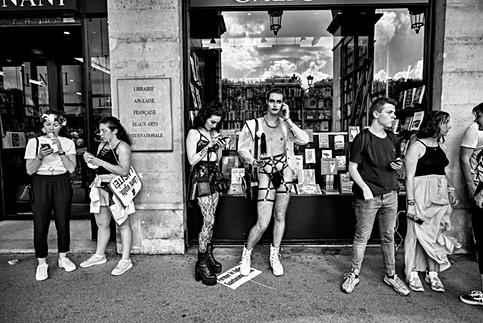 gaypride de paris un drag queen est entouré de gens , il est au téléphone avec un ami