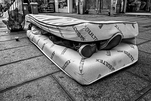 dans une rue de paris un sans-abri dort dans un matelas de lit fermé en deux, la photo en noir et blanc est triste