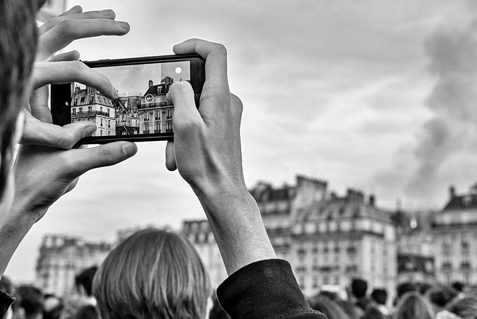 fire in Paris cathedral notre dame a man takes photos with his iphone, black and white photo