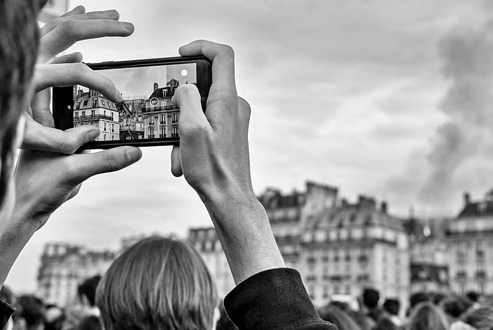 incendie de la cathédrale de paris un homme fait des photos avec son iphone, photo noir et blanc