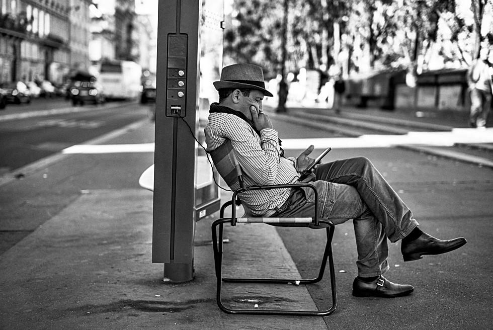 à paris un bouquiniste recharge son téléphone portable sur du mobilier urbain, consulte ses mail en même temps, photo noir et blanc