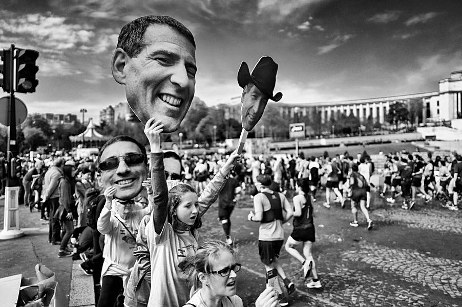 the paris marathon, a young girl wears pictures of her dad to encourage him, black and white