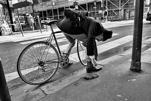 un homme dans une rue de paris avec son vélo, il s'est arreté pour refaire son lacet de chaussure