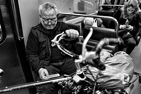 dans le métro de paris un homme consulte son téléphone, il a son vélo avec lui, une femme derriére lui est au téléphone aussi