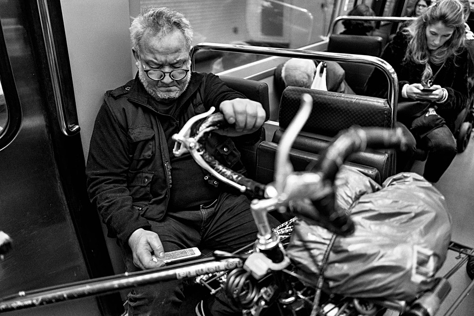 in the Paris subway a man consults his phone, he has his bike with him, a woman behind him is on the phone too