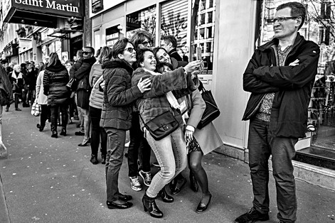 in front of a theater a group of women take a selfie with their smartphone, a man is in front of them, phone addiction