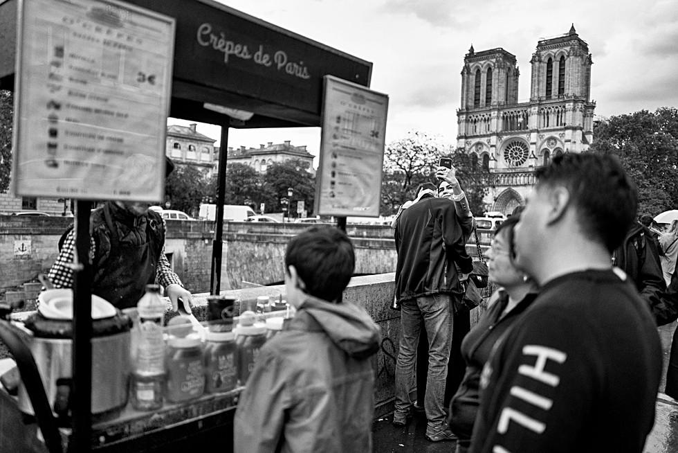 un couple de touriste fait un selfie devant la cathédrale notre dame à paris