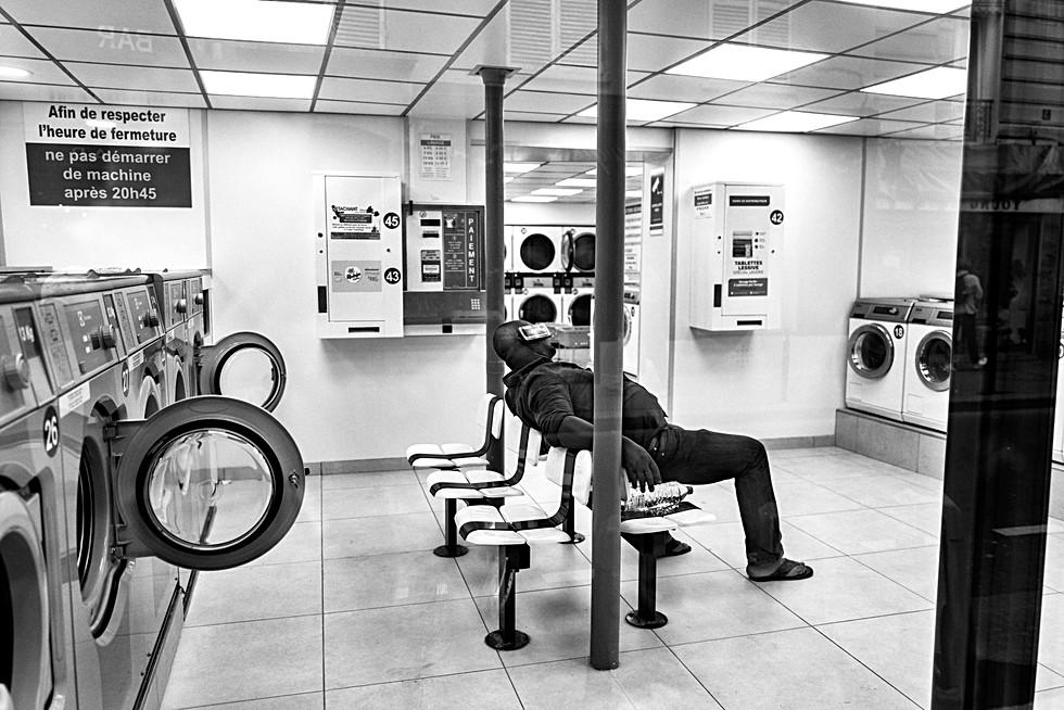 dans une laverie automatique un homme parle avec son téléphone portable, nomophobe