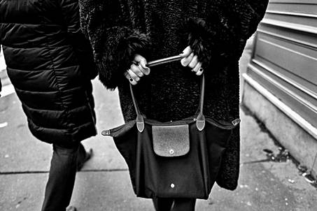 paris france, a street photo by laurent delhourme, a woman walking seen from the back holds a handbag, black and white at leica q