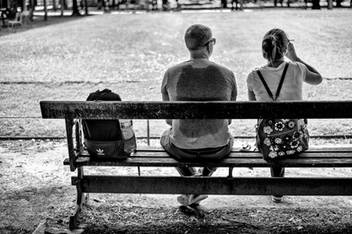 paris jardin des tuileries on a bench a couple is sitting and having a drink it is very hot, the man has a trace of perspiration from his backpack on his t-shirt
