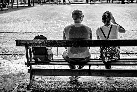 paris jardin des tuilleries sur un banc un couple est assi et se desaltére il fait très chaud, l'homme a une trace de transpiration de son sac à dos sur son t-shirt, photo noir et blanc de laurent delhourme