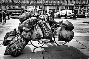 homeless with a big beard who lives in the street pushes his bike, he has a lot of bags, he crosses the place de la République in paris