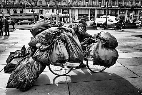 un sdf traverse la place de la république de paris, il pousse son vélo il porte beaucoup de sacs, photo humaniste de laurent delhourme