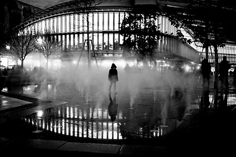 in front of the halles de paris a child plays under a fogger, graphic photo in black and white at night, humanist photograph made by laurent delhourme