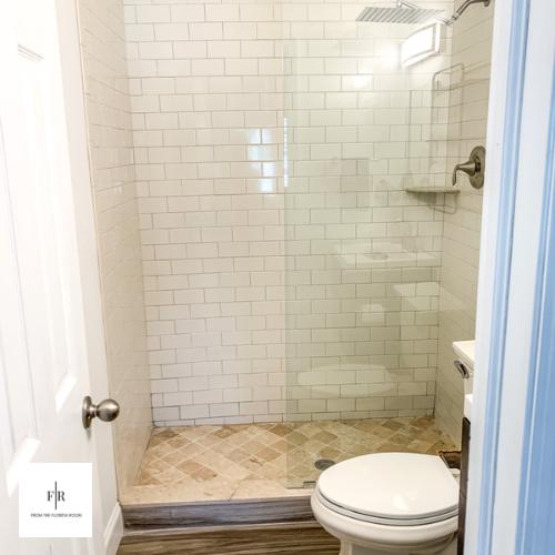 Frameless glass shower panel with large rain shower head