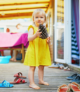 child in yellow dress holding pine cone