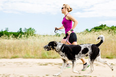 Woman runner running with dog on country