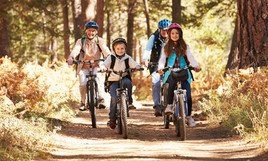 Grandparents and kids cycling on forest