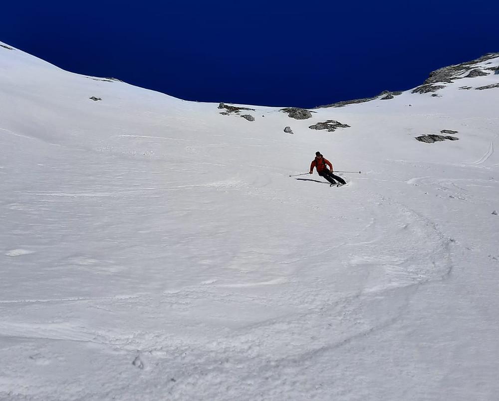 Ein Bergführer macht einen Schwung mit seinen Skiern im Butterfirn