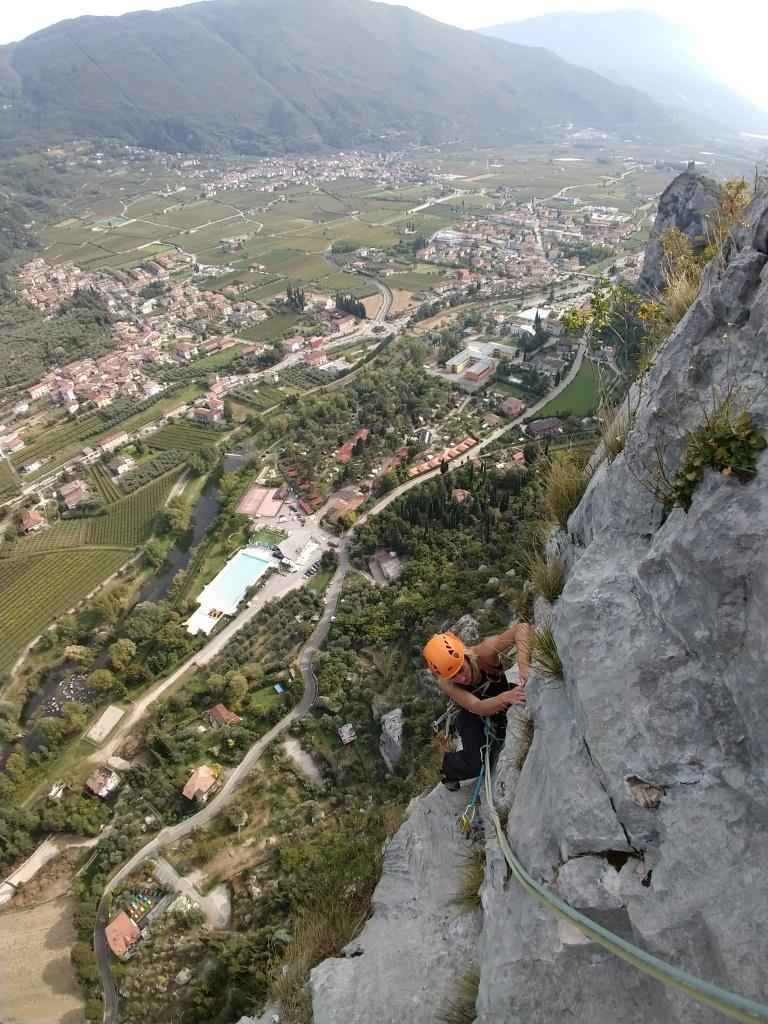 Blick in die Tiefe auf eine Kletterin mit Arco im Hintergrund