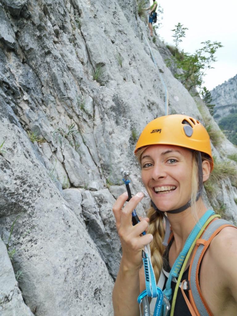 Kletterin zeigt einen Friend in die Kamera